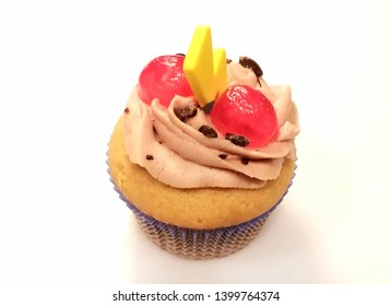 Cappucino cupcake with a yellow candy and a red cherry on top