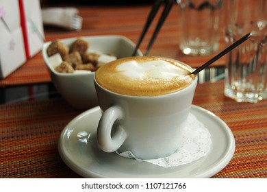 Cappucino foam in the white cup and saucer, suger, spoon