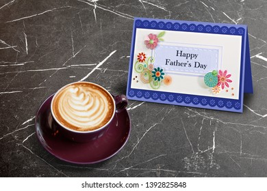 Cappucino with heart shape and Handmade scratch greeting card with Happy Father day text on Textured Black marble table