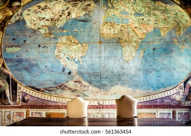 Caprarola, Italy 21 Apr 2013 - freemasonry controlling world , a big table with two empty chairs and  an old world map on the wall