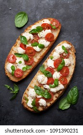 Caprese bruschetta toasts with cherry tomatoes, mozzarella and basil. Top view
