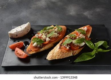 Caprese bruschetta toasts with cherry tomatoes, mozzarella and basil. Appetizers with Italian antipasti snacks.