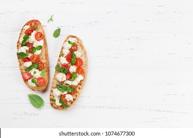 Caprese bruschetta toasts with mozzarella, cherry tomatoes and fresh garden basil. Top view with space for your text