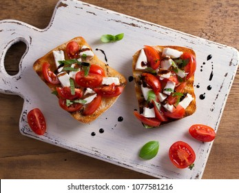 Caprese Bruschetta. Tomatoes, basil, mozzarella cheese with balsamic reduction drizzle on toast. Antipasto - starter dish. View from above, top