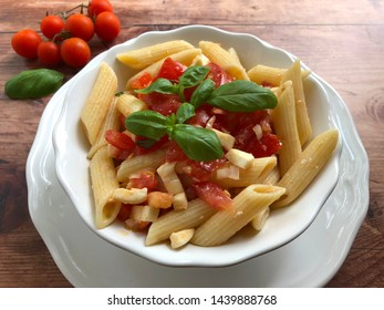Caprese pasta salad is a incredibly popular classic summer dish. Caprese pasta salad  with tomatoes,  mozzarella cheese,  basil, olive oil, dressing and herbs on rustic wooden background.