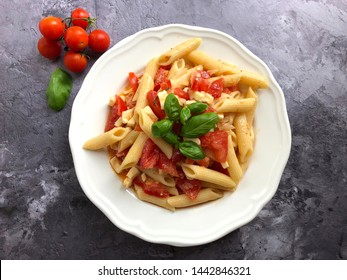 Caprese pasta salad is a incredibly popular classic summer dish. Caprese pasta salad  with tomatoes,  mozzarella cheese,  basil, olive oil, dressing and herbs on stone background.