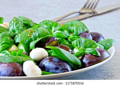 Caprese salad with blue plums. Keto diet. The idea keto lunch. Vegan lunch idea. Fitness salad Caprese. Healthy and beautiful salad a la caprese.