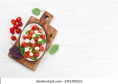 Caprese salad with cherry tomatoes, mozzarella and basil. Top view with space for your text
