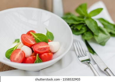 Caprese salad with cherry tomatoes, mozzarella and basil leaves in a white plate