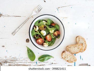 Caprese salad and chiabatta slices. Cherry-tomatoes, baby spinach and mozzarella in metal bowl with pesto dressing on rustic white wooden backdrop, top view, horizontal