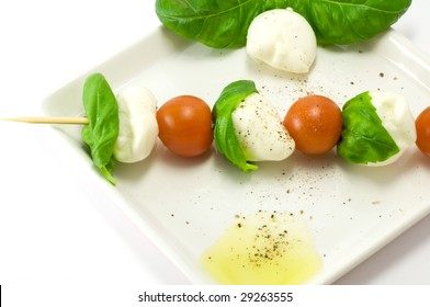 Caprese salad close-up with olive oil green basil and  pepper