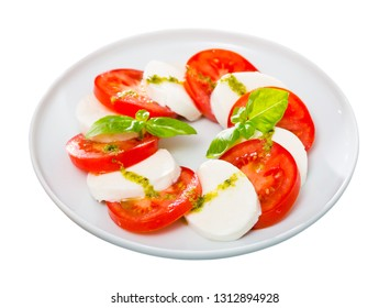 Caprese salad with fresh tomatoes, mozzarella cheese and basilic herb, dish of Italian cuisine. Isolated over white background