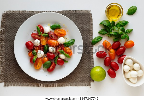 caprese salad and its ingredients on a white background
