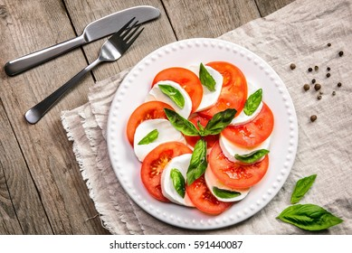 Caprese salad made of mozzarella cheese, tomatoes and basil leaves on a wooden background. Top view.