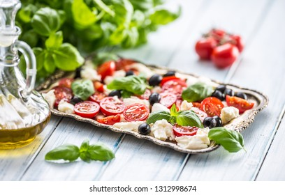Caprese salad with mozzarella cheese ripe tomatoes olives and basil leaves. Italian or mediterranean healthy meal.