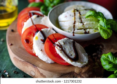 Caprese salad. Mozzarella cheese, tomatoes and basil herb leaves