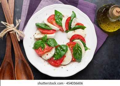 Caprese salad. Mozzarella cheese, tomatoes and basil herb leaves on plate over stone table. Top view