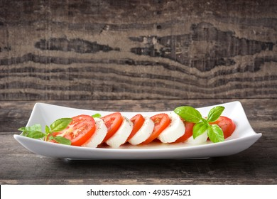 Caprese salad with mozzarella cheese, tomatoes and basil isolated on rustic wooden background