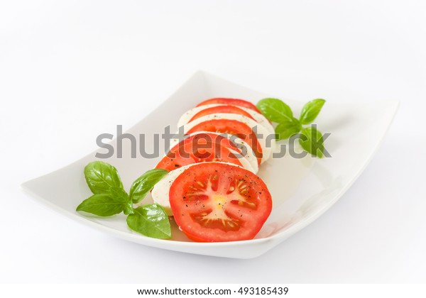 Caprese salad with mozzarella cheese, tomatoes and basil isolated on white background