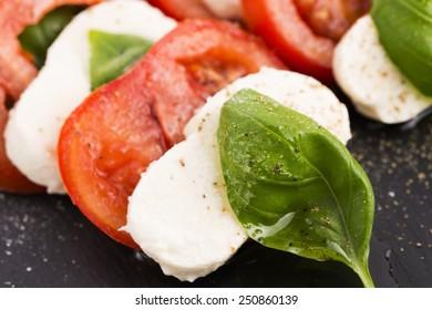 Caprese salad with mozzarella, tomato, basil and balsamic vinegar arranged on black plate