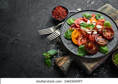 Caprese salad on a black plate. Tomatoes, mozzarella cheese and basil. Top view. Free space for your text.