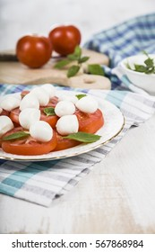 Caprese salad on a wooden table. Delicious salad with mozzarella, tomato and basil.