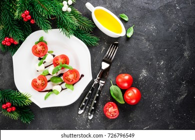 Caprese salad in the shape of christmas tree. Festive appetizer on dark table. Christmas table setting concept with salad caprese. Christmas background. Top view, Copy space