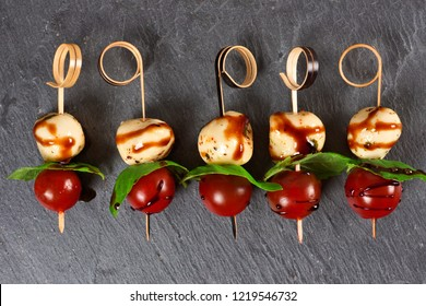 Caprese salad skewers with mozzarella, basil, tomatoes and balsamic glaze. Appetizers against a dark stone background.