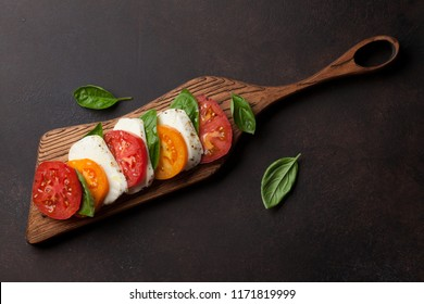 Caprese salad with tomatoes, basil and mozzarella. Top view and flat lay with copy space