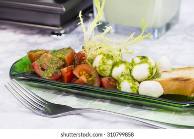 Caprese salad with tomatoes and cheese in a plate of glass