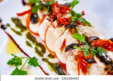 Caprese salad with tomatoes, mozzarella cheese, pesto sauce and black olives on white plate. Close up