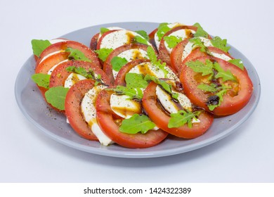 Caprese salad tomatoes mozzarella cheese basil olive oil pepper sauce. Gray plate with caprese on white. Italian cuisine, Mediterranean recipe for fresh vegetarian vegetable salad