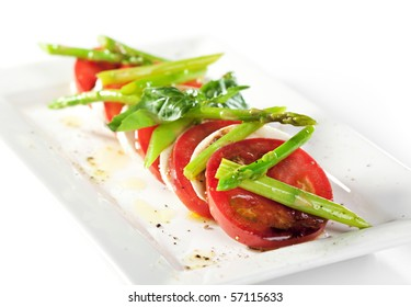 Caprese Salad - Salad with Tomatoes, Mozzarella Cheese, Green Asparagus and Basil Leaf