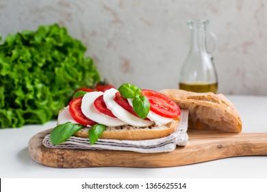 Caprese sandwich: Mozzarella, tomatoes, basil leafes, italian bread, olive oil. Olive oil bottle.