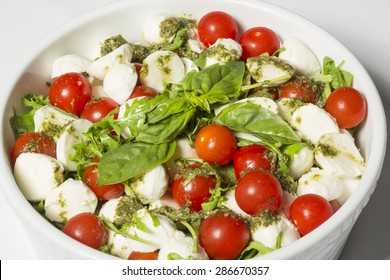 Caprese served with pesto and basil leaves