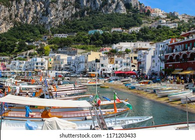 Capri, Italy 2015-06-27 Busy beach with boats docked and people walking in the island of Capri , Italy