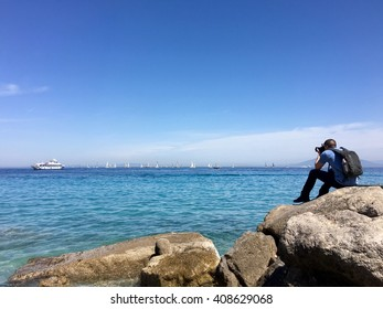 CAPRI, ITALY - APRIL 15, 2016: A photographer taking a picture of the sail boats in the bay at the port. Capri is a beautiful island of Italy.