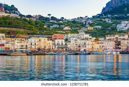 Capri, Italy - April 23, 2018: Marina Grande after sunset, Capri island, Italy. Illuminated streets of city are reflected in calm sea.
