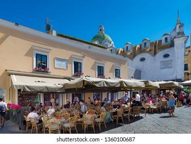 CAPRI, ITALY - APRIL 23, 2018 : Unknown tourists at outdoor restaurant in Capri island, Italy.