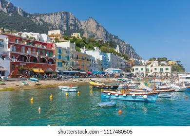 Capri, Italy - April 25, 2018: Crowd of tourists walk along Marina Grande, fishing boats are floating in clear sea in sunny day at Capri Island, Italy