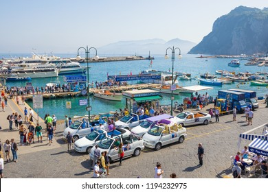 Capri, Italy - April 25, 2018: Crowd of tourists walk along Marina Grande, sightseeing boats, ferry and taxi at Capri Island, Italy