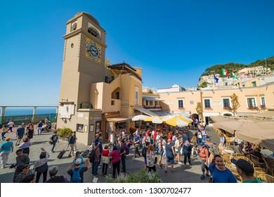 Capri, Italy - April 25, 2018: Tourist walking near clock tower on Piazza Umberto, knows as La Piazzetta, Capri Island, Italy