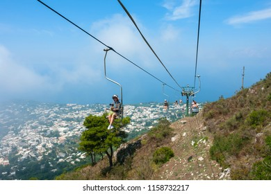 CAPRI, ITALY - July 29, 2018: Tourists riding up the mountain lift. Capri is a popular tourist destination and an island of Italy.