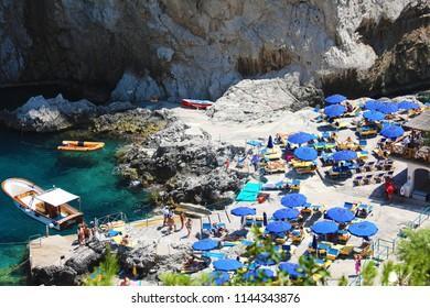 CAPRI, ITALY - JULY 4, 2018: rocky beach between Faraglioni cliffs of Capri, Italy