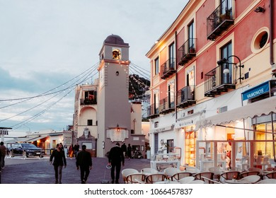 CAPRI, ITALY, MAY 10, 2017: Clock tower of Church of Santo Stefano and nearest cafes at Piazza Umberto I in the evening.