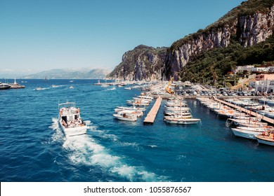 CAPRI, ITALY - May, 13, 2017: Marina Grande pier - excursion boats taking numerous tourists on trips around the island on a bright spring day.