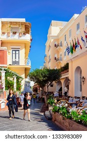 Capri, Italy - October 3, 2017: People at Street cafe and restaurant table and chair on Capri Island, Naples, Italy. Landscape with Cafeteria, Italian coast. Anacapri in Europe. View in summer. Amalfi