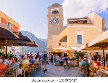 Capri, Italy - October 3, 2017:  People at Piazza Umberto I Square with Church of Santo Stefano in old town of Capri Island town at Naples, Italy. Landscape at Italian coast. Anacapri in summer Amalfi