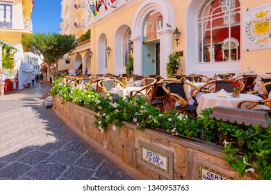 Capri, Italy - October 3, 2017: Street cafe and restaurant table and chair on Capri Island, Naples, Italy. Landscape with Cafeteria, Italian coast. Anacapri in Europe. View in summer. Amalfi scenery