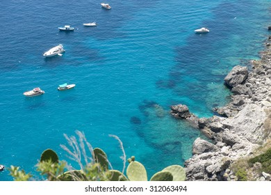CAPRI, ITALY-JUNE 26, 2015: top view of the island rocky coast line with boats and yachts on the beautiful emerald sea, in Capri.